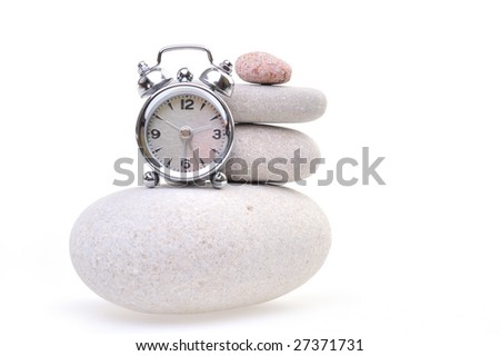 alarm clock over stone against white background - stock photo