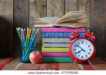 Alarm clock, pencils and a stack of books. Back to school. Still life with books.