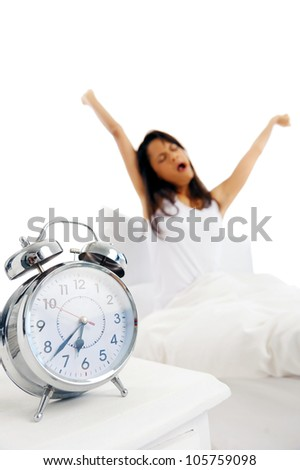 Alarm clock ringing with time to wake up, woman stretching and yawning in the background. focus on alarm clock. - stock photo