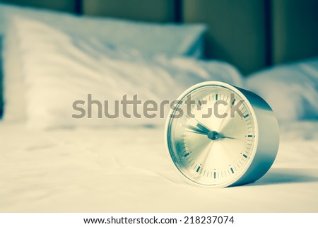 Alarm clock set on the couch - stock photo