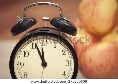 alarm clock showing almost twelve o'clock with red and yellow apples on the background. extreme closeup - stock photo