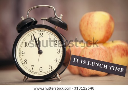 alarm clock showing almost twelve with red and yellow apples surrounding it and indicating it is lunch time. closeup. selective focus - stock photo
