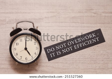 alarm clock showing five and indicating not to overwork as it is not efficient - stock photo