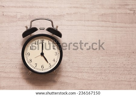 alarm clock showing five o'clock on wooden background - stock photo