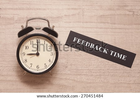 alarm clock showing nine and sign indicating feedback time on wooden background - stock photo