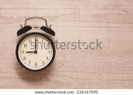 alarm clock showing nine o'clock on wooden background - stock photo