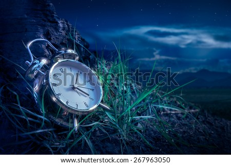 alarm clock sitting in the grass at night - stock photo
