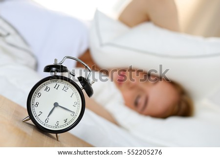 Alarm Clock Standing On Bedside Table Going To Ring While Woman Cover Head  And Ears With