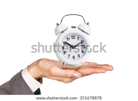 Alarm clock stands on the human palm isolated on white background
