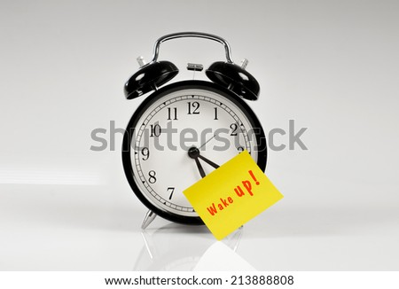 Alarm clock with a yellow note saying wake up - stock photo