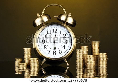 Alarm clock with coins on dark background - stock photo