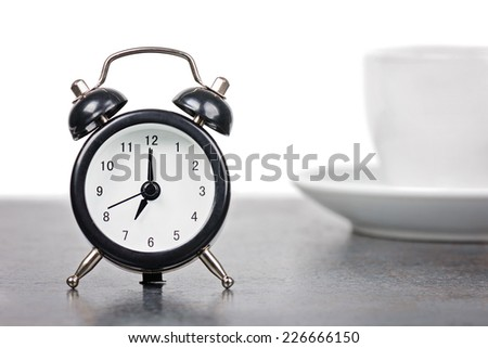 Alarm clock with cup of coffee - stock photo