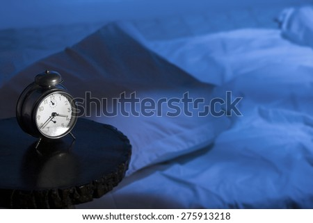 Alarm clock with empty bed and moon-light effect.  - stock photo