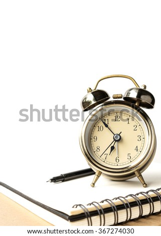 Alarm clock with empty notebook and white background, selective focus - stock photo