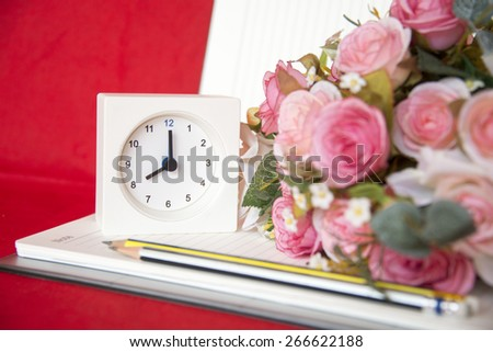 alarm clock with flowers and notebook - stock photo