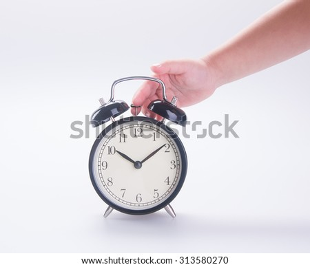 alarm clock with hand. alarm clock with hand on background.