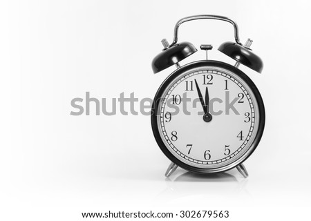 Alarm clock with 3 min before 12 o`clock on white background