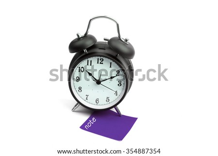 Alarm clock with note purple sticky paper - stock photo