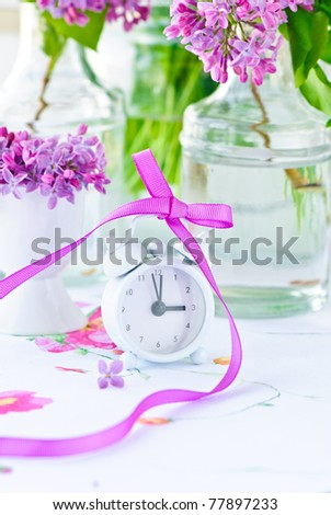 alarm-clock with purple ribbon and spring flowers on white napkin - stock photo