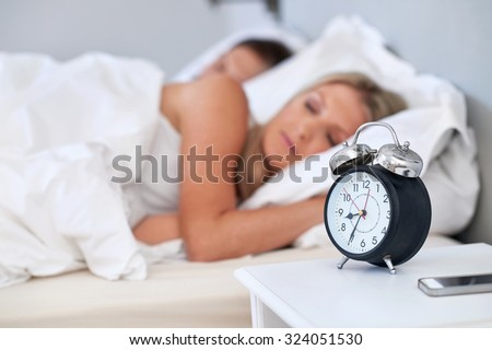 alarm clock young couple sleeping comfortably in bed at home - stock photo