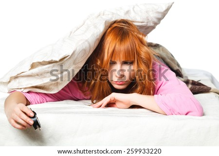 alarm clock. Young woman in the background covering ears with pillow. room clock bed lazy sleep wake alert - stock photo