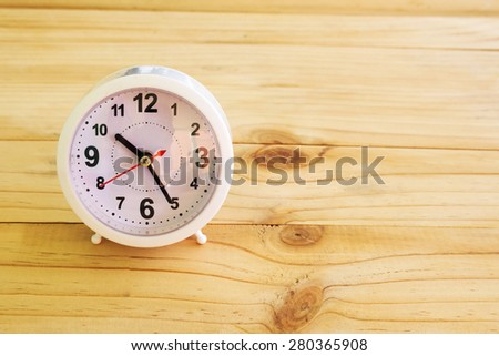Alarm clockon wooden background - stock photo