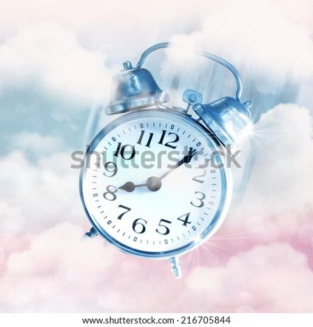 Alarm clocks flying on blue sky, time flies concept. - stock photo