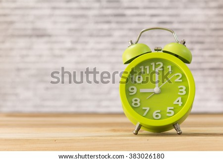 alarm clocks on wooden table in the office. - stock photo