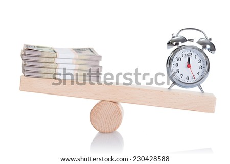 Alarmclock and dollar bundles balancing on seesaw isolated over white background - stock photo