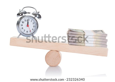 Alarmclock and stacked dollar bundles balancing on seesaw isolated over white background - stock photo