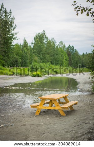 Alaska forest wilderness with wooden picnic table for eating meals. - stock photo