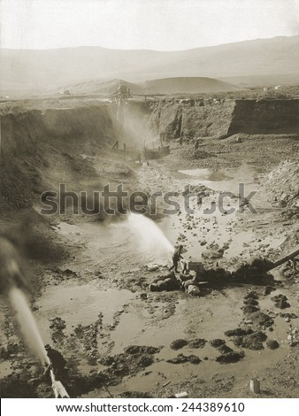 Alaskan hydraulic gold mining used jets of water to erode rock material or move sediment. The resulting water-sediment was then directed through sluice boxes to remove the gold.Ca. 1900-1923. - stock photo