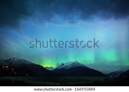 Alaskan northern lights at night with stars and clouds with snow covered mountains and water in the foreground. - stock photo