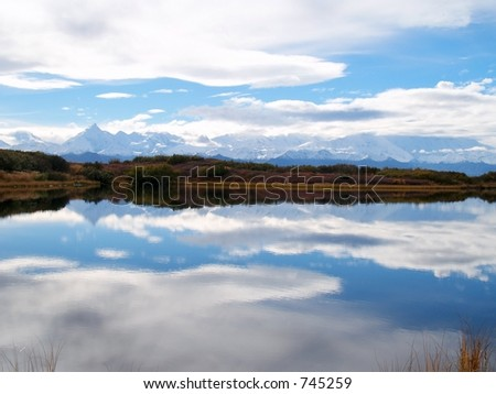 Alaskan range (including Denali) and sky reflected in a still mountain pond - stock photo