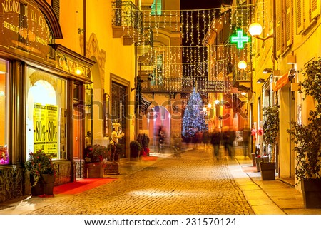 ALBA, ITALY - DECEMBER 30, 2013: Pedestrian street and shops in old town illuminated for Christmas and New Year holidays. This area is very popular with locals and tourists visiting Alba for holidays. - stock photo