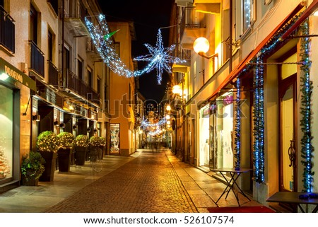 ALBA, ITALY - DECEMBER 07, 2011: Pedestrian street and shops in Old Town of Alba illuminated and decorated for Christmas. This area is very popular with locals and tourists visiting the town.