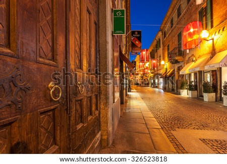 ALBA, ITALY - DECEMBER 30, 2014: Wooden door and illuminated pedestrian street with shops at Christmas time. This area is popular with locals and tourists visiting Alba for winter holidays. - stock photo