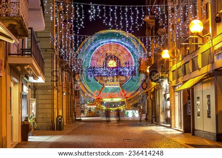 ALBA, ITALY - jANUARY 03, 2013: Decorated street and illuminated observation wheel in old town of Alba as part of traditional Christmas and New Year celebrations. - stock photo