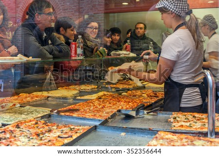 ALBA, ITALY - NOVEMBER 15, 2015: People inside typical pizzeria bying pizza - traditional italian dish invented in Naples, very popular in all over the world. - stock photo