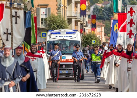ALBA, ITALY - OCTOBER 05, 2014: Warriors in historic dresses and carabiniers on background march through streets of Alba during traditional annual Medieval Parade. - stock photo