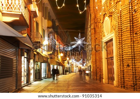 Alba old town central street with opened shops, bars and stores and illuminations for Christmas and New Year holidays. - stock photo