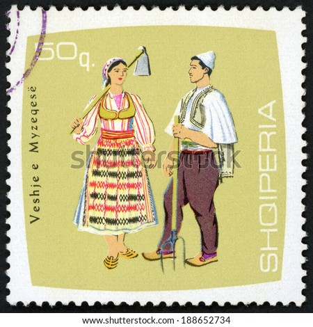 ALBANIA - CIRCA 1967: post stamp printed in Albania (shqiperia) shows farm couple holding pitchfork and hoe, Myzeqese  from regional costumes, Scott 1055 A227 50q multicolor, circa 1967 - stock photo