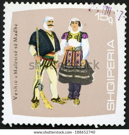 ALBANIA - CIRCA 1967: post stamp printed in Albania (shqiperia) shows man and woman from Madhe; farmer holding riffle, regional costumes series, Scott 1051 A227 15q violet, circa 1967 - stock photo