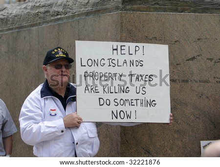 "ALBANY, NY - JUNE 16: A protester against wasteful government spending and corrupt career politicians holds a sign during the Tea Party Patriots ""March on Albany"" protest on June 16, 2009 in Albany NY"