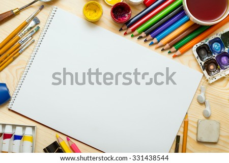 Album pages and paints, pencils,oil, brush on a wooden background  - stock photo