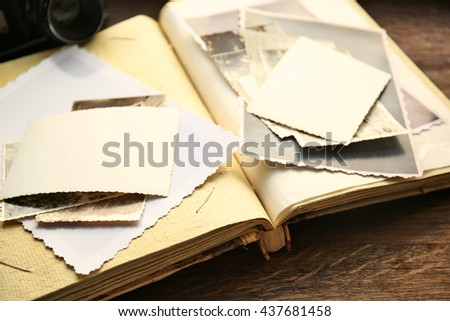 Album with vintage photos and camera on wooden background - stock photo