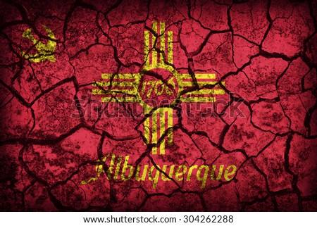 Albuquerque ,New Mexico flag pattern on crack soil texture,retro vintage style - stock photo
