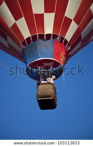 ALBUQUERQUE, NM - OCTOBER 01: Hot Air Baloon Fiesta in Albuquerque, New Mexico. Young man ascending in red and white baloon. Seen with blue sky in the background on October 1, 2011.