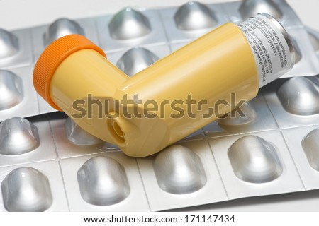 Albuterol asthma inhaler with medication in blister packs. - stock photo