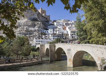 Alcala del Jucar, Spain - October 29, 2016: Roman bridge, located in the central part of the town, to its passage by the river Jucar, at the top of mountain is situated castle, Alcala del Jucar, Spain